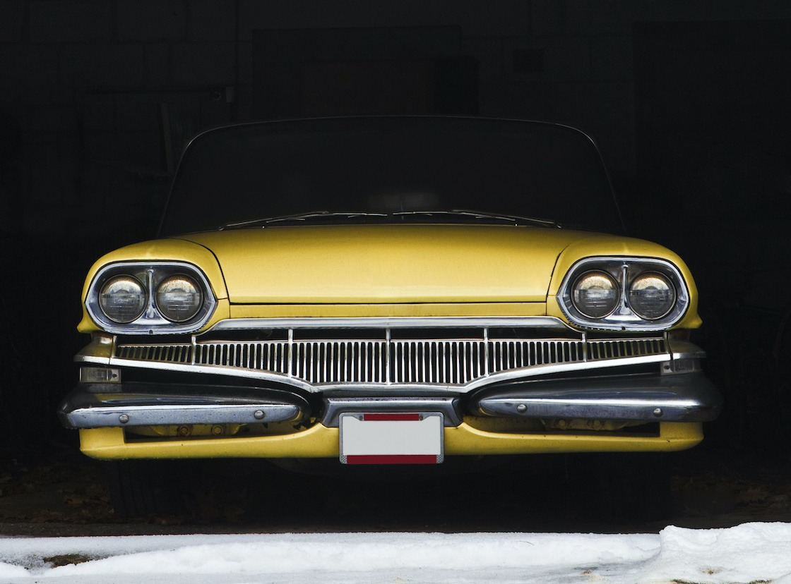 Vintage car is wrapped and placed in a secure car storage facility for winter.