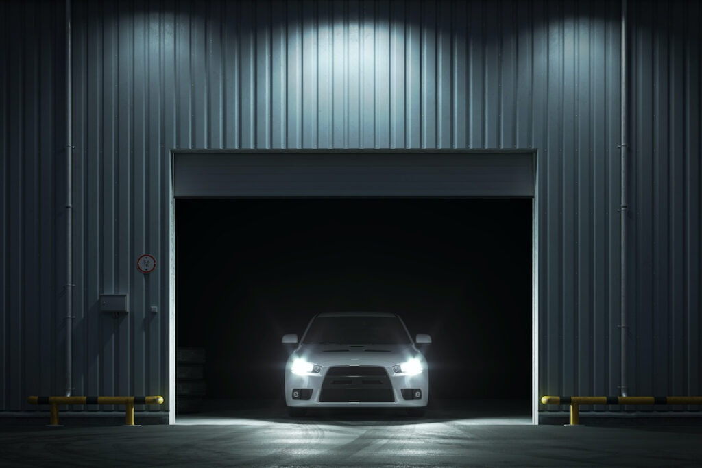 Car with headlights on in luxury car storage facility