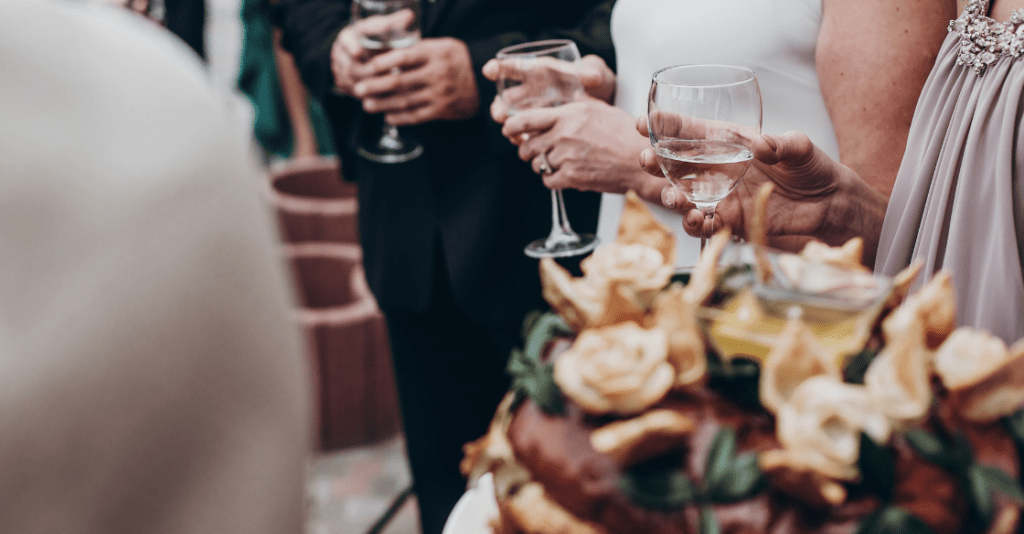 luxury life concept. champagne and wine glasses in hands at luxury wedding reception at restaurant. guests toasting and cheering at stylish celebration.