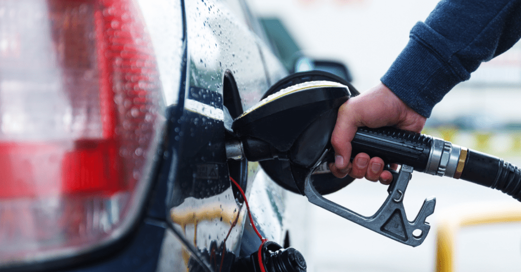 A man fills the tank on his car with gasoline.