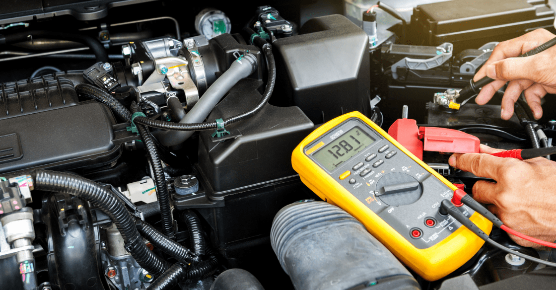 A man uses a multimeter to check his car battery as part of routine summer maintenance.