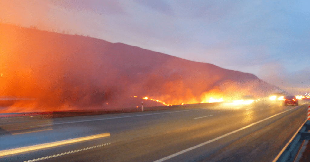 Cars drive past a wildfire on a California highway.